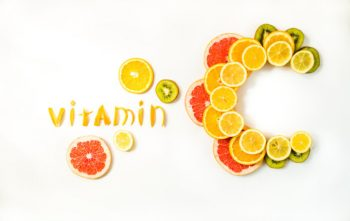 Vitamin C letters made of citrus fruits - lemon, grapefruit, orange and kiwi slices on white background